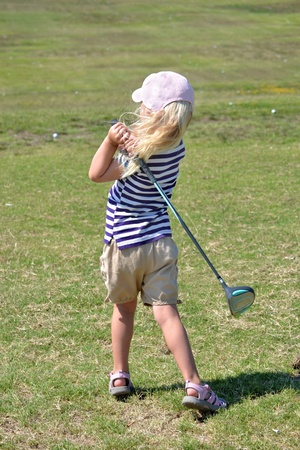 little girl hitting golf balls