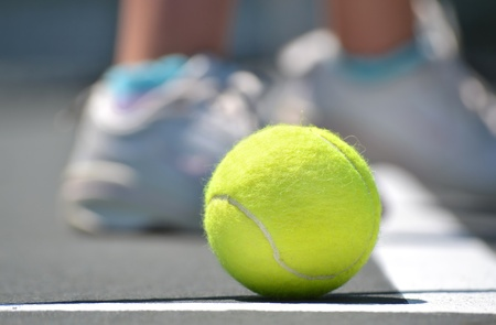 close of tennis ball on court and feet photo