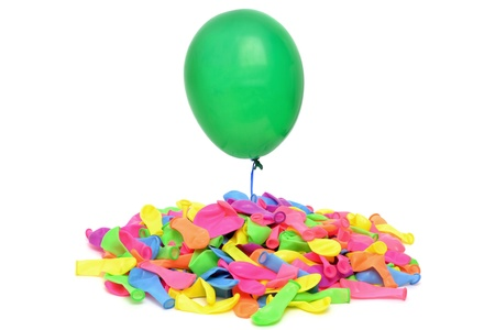 floating green balloon over pile of balloons