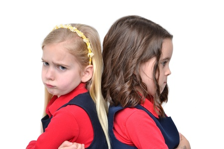 scowl: two girls sitting back to back Stock Photo