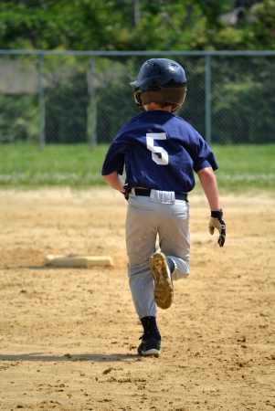 fast foot: youth baseball player running bases