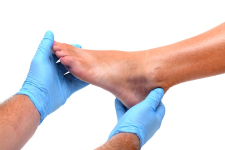 医師が負傷した足を調べる