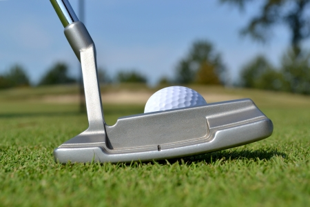 close of putter and golf ball on green photo