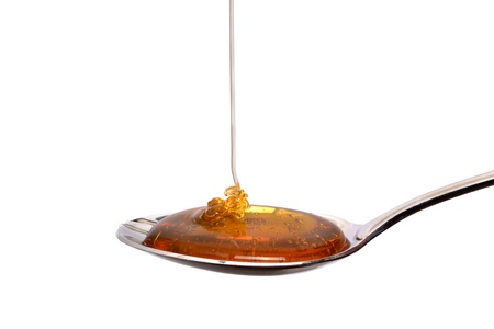 pouring honey on spoon white background Banco de Imagens