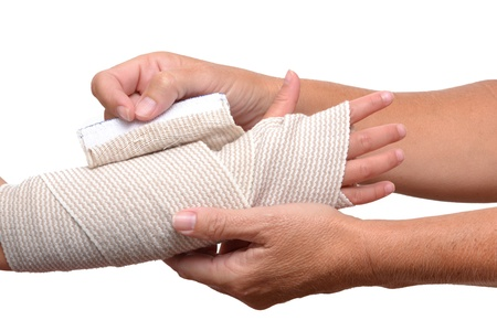 hands wrapping bandage on childs arm Stock Photo