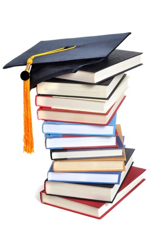 stacked books: stacked books and a graduation hat with honor tassel Stock Photo