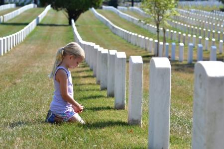 curare teneramente: giovane ragazza pregando in cimitero Archivio Fotografico