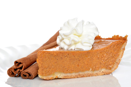 slice of pumpkin pie with whipped topping and cinnamon sticks isolated on white background photo