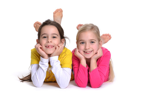 silliness: two girls lying on stomach white background Stock Photo