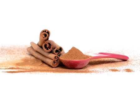 measuring spoon: cinnamon sticks and measuring spoon isolated white background