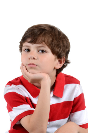 hand on the chin: young boy with leaning chin in hand isolated white background