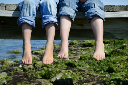 dirty feet: two barefoot boys in jeans sitting on dock Stock Photo