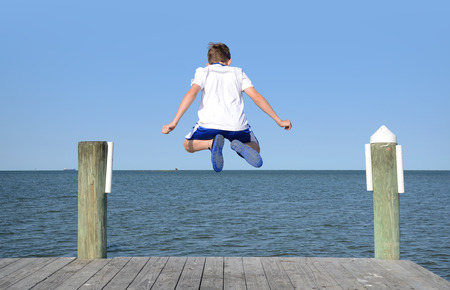 Jongen springen in de lucht van de dok in water Stockfoto