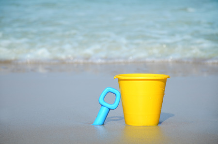 sand bucket and shovel in the sand by the water Zdjęcie Seryjne