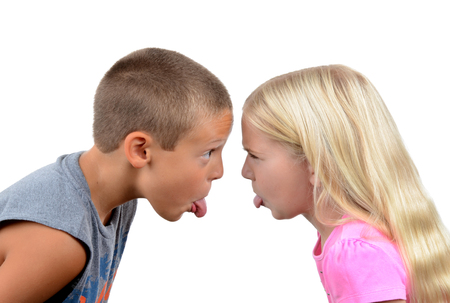 playful behaviour: girl and boy sticking out their tongues at each other isolated white background