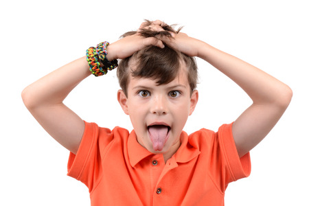 rowdy: young boy with hands in hair and tongue sticking out isolated white background