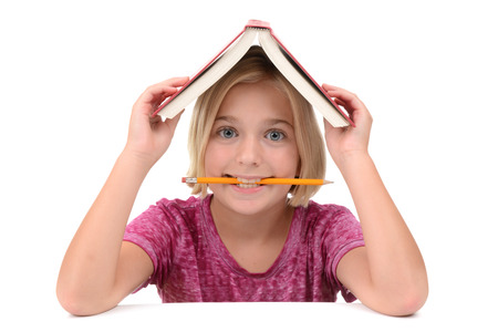 young girl with a book on her head and pencil in mouth photo