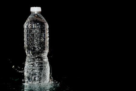 plastic water bottle on wet black background