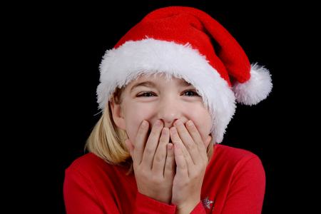little girl with santa hat and hands over mouth excitement concept photo