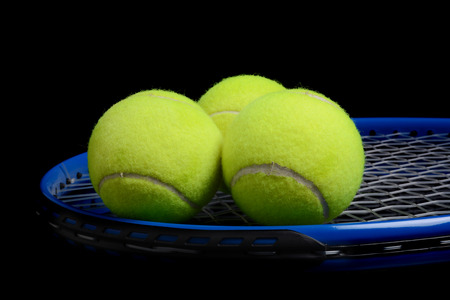 sport object: tennis balls and tennis racket black background