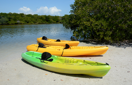 three kayaks on the shore of a river