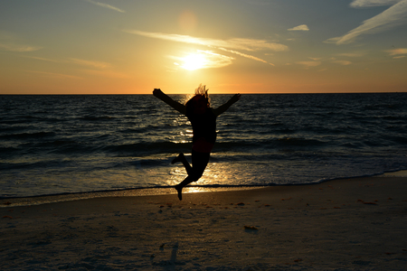 young girl jumping on the beach at sunset photo