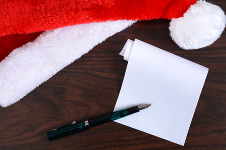 Santa hat on desk with pen and paper Christmas concept Zdjęcie Seryjne