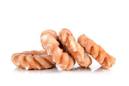 four glazed cruller donuts in pile isolated white background