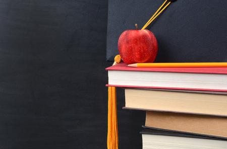School graduation cap with apple books and blackboard Zdjęcie Seryjne