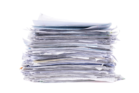 messy stacked pile of paperwork isolated on white background Imagens
