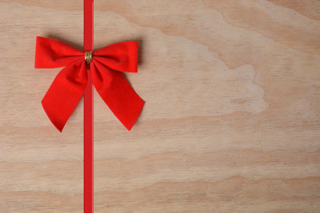 red christmas bow and ribbon on wood background holiday concept