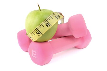 pink dumbbells green apple and tape measure isolated on white background