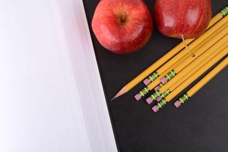 open book,pencils,apples on a blackboard educational concept Zdjęcie Seryjne