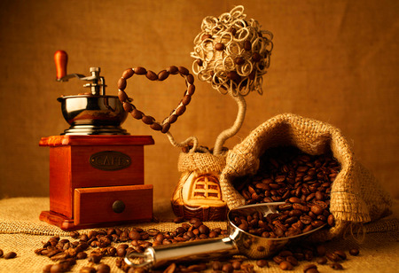 sacking: roasted coffee beans, vintage coffee-mill on sacking background