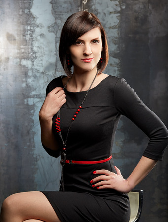 brown  eyed: Beautiful slim woman. Professional make up. Black dress, red manicure, red belt, red necklace.