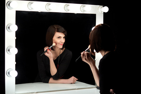 brown  eyed: Beautiful woman. Professional makeup. Black dress, red manicure, red necklace. Makeup mirror with light bulbs. Makeup brush. Stock Photo