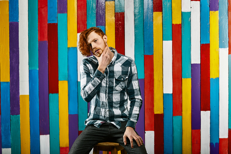 Red Hair Models. Bearded man. Portrait. Young Redhead man in plaid shirt on colourful background. Young thoughtful redhead bearded.