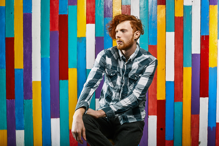 plaid shirt: Red Hair Models. Bearded man. Portrait. Young Redhead man in plaid shirt on colourful background. Young thoughtful redhead bearded.