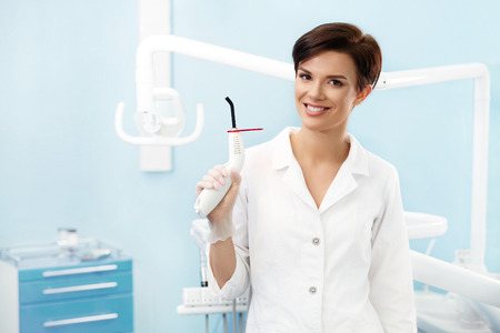 sealant: Young female doctor in dentist office.Beautiful smiling woman in white lab coat holding blue dental curing light.Dental clinic.Stomatology