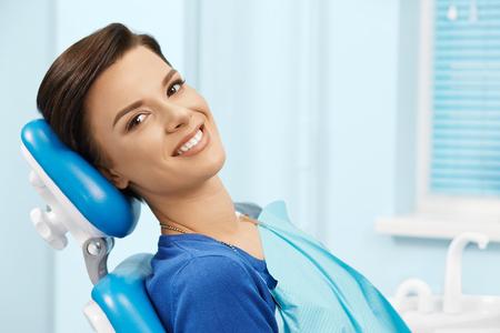 Jeune patiente dentiste visite office.Beautiful femme souriante avec des dents blanches droites en bonne santé assis à dentaire chair.Dental clinic.Stomatology Banque d'images - 75641092