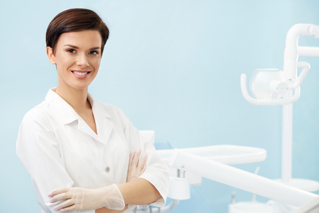 歯科医のオフィスで若い女医。白衣で笑顔美人歯科医院。口腔病学