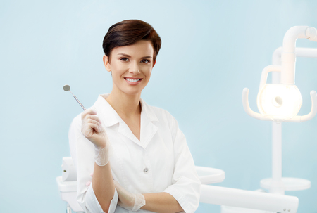 Young female doctor in dentist office.Beautiful smiling woman in white lab coat holdingdental mirror.Dental clinic.Stomatology