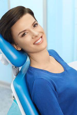 若いメスの患者は歯科医のオフィスを訪問します。歯科用の椅子に座って健康ストレート白い歯と美しい笑顔の女性。歯科医院。口腔病学 写真素材