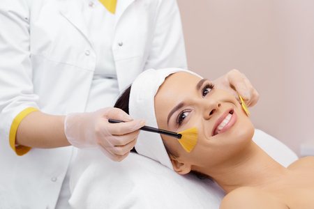 Cosmetology. Spa clinic. Beautiful woman at facial treatment procedure. Young healthy skin. Facial mask. Skin rejuvenation. Stock Photo