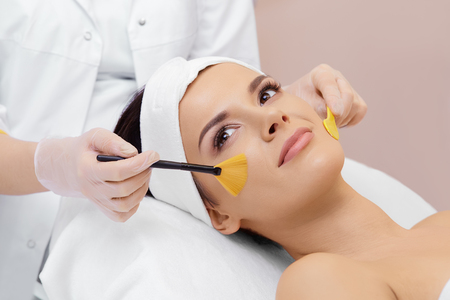 Cosmetology. Spa clinic. Beautiful woman at facial treatment procedure. Young healthy skin. Facial mask. Skin rejuvenation. Stok Fotoğraf