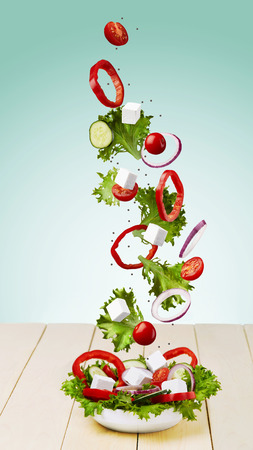 Flying food. Fresh appetizing salad on a wooden table. Flying salad. Stock Photo