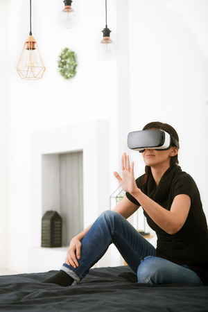 Virtual reality today. Young woman in the world of virtual reality. Smartphone using with VR glasses. Stok Fotoğraf