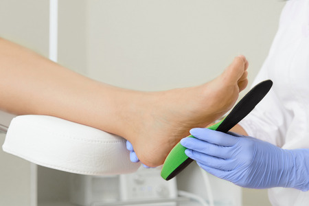 Orthopedic insoles. Fitting orthotic insoles. Flatfoot treatment. Podiatry clinic.  Stock Photo