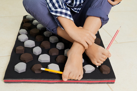 Little boy on massage mat doing exercises for flatfoot prevention.Child flatfoot treatment using special massage carpet.Foot strengthening exercises.Podiatry clinic.  Archivio Fotografico