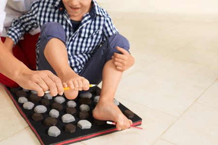 Little boy on massage mat doing exercises for flatfoot prevention.Child flatfoot treatment using special massage carpet.Foot strengthening exercises.Podiatry clinic.  Stock Photo